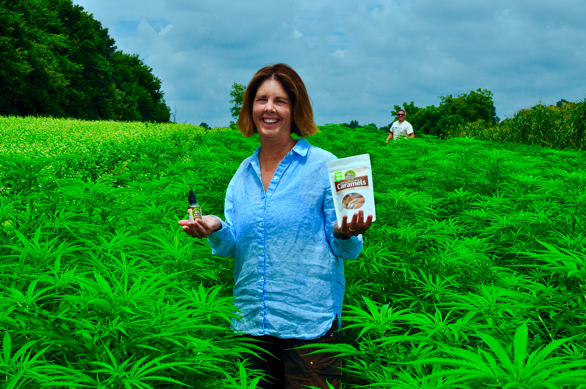 Laura Freeman standing in organic hemp field holding Homestead Alternatives Full Spectrum CBD Oil and Caramels.